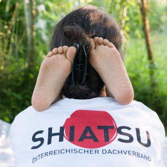 Kinderfüße auf der Schulter der Shiatsupraktikerin